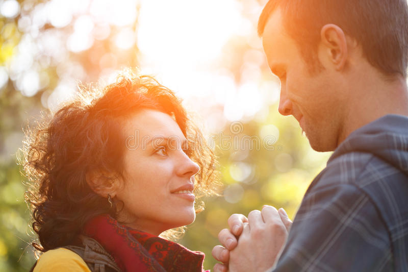 Houdend van paar in het park die elkaar binnen bekijken stock afbeelding
