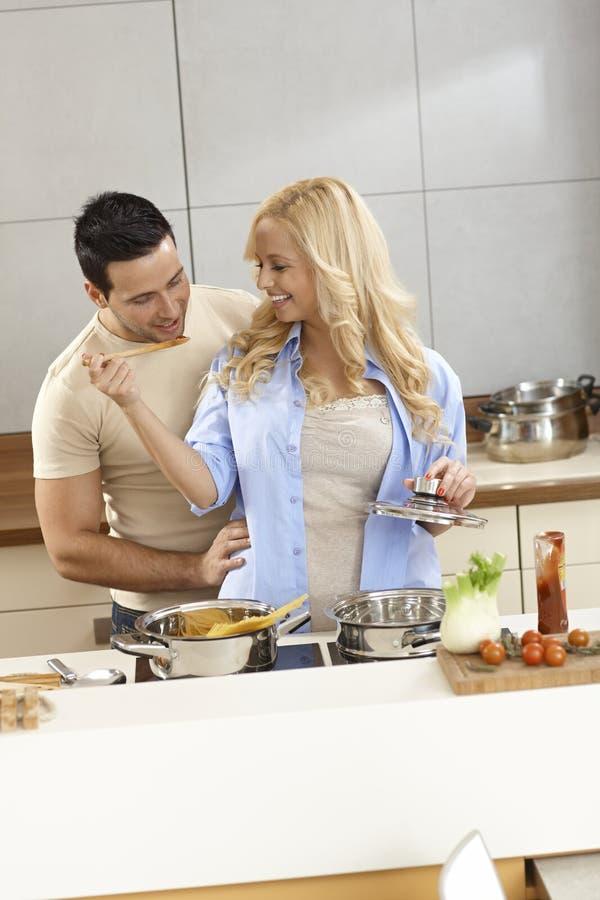 Houdend van paar kokend en proevend voedsel in keuken stock afbeeldingen
