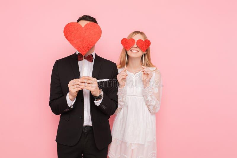 Houdend van paar in liefde, man en vrouw met rode harten op hun ogen, over roze achtergrond Het concept van de minnaarsdag royalty-vrije stock foto's