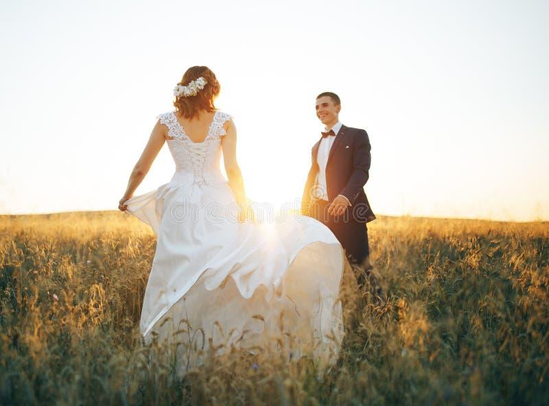 Houdend van paar op het gebied van tarwe in de zonsondergang stock afbeelding