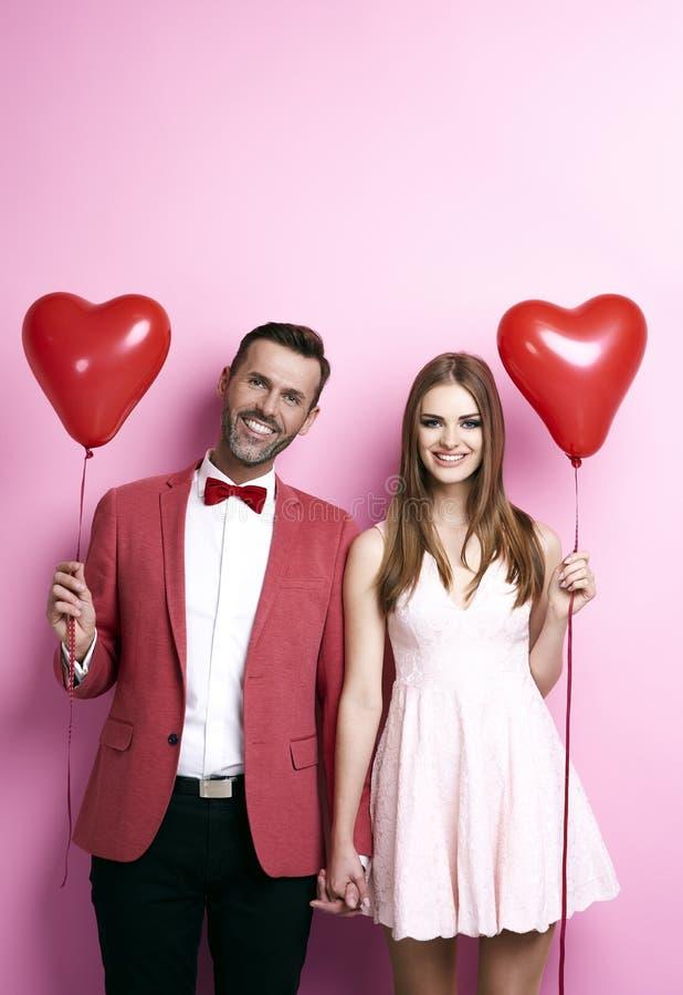 Houdend van paar tijdens valentijnskaart` s partij stock foto