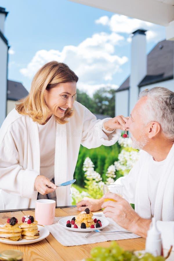 Houdend van richtend paar die buiten witte badjassen dragen die ontbijt hebben stock foto