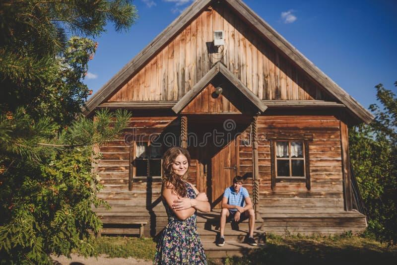 Houdend van romantisch paar in het dorp, dichtbij een blokhuis Een man zit op de portiek, een jonge vrouw in de voorgrond royalty-vrije stock foto