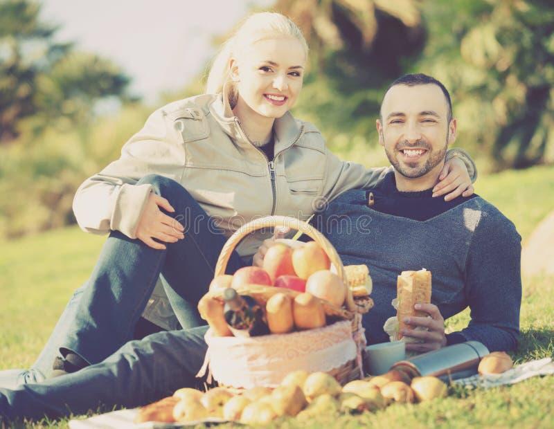 Houdend van vrolijk jong paar die zoals hebbend picknick babbelen royalty-vrije stock fotografie