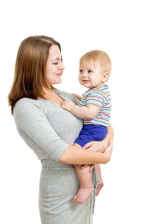 Houdende van de babyjongen van de moederholding die op wit wordt geïsoleerde stock afbeeldingen