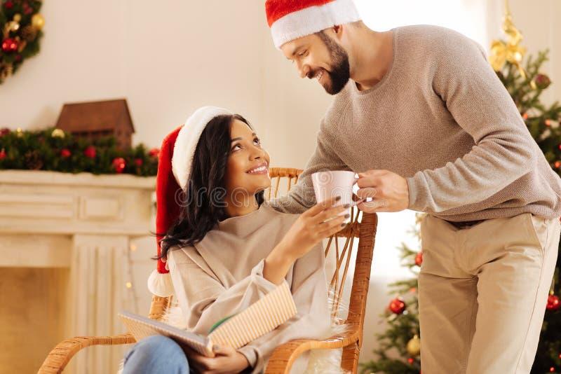 Houdende van echtgenoot die koffie geven aan zijn vrouw terwijl zij lezing royalty-vrije stock foto's