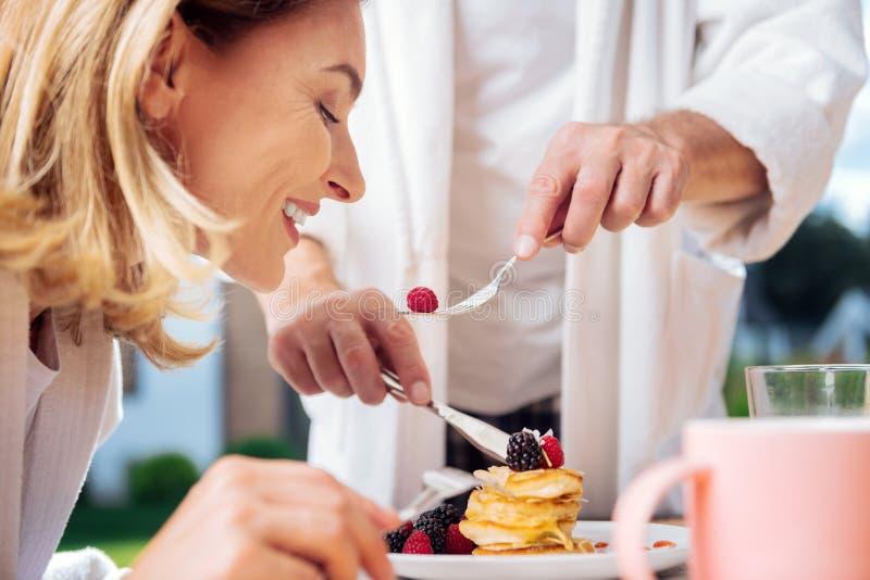 Houdende van echtgenoot die pyjama dragen die zijn mooie blonde-haired vrouw voeden royalty-vrije stock foto