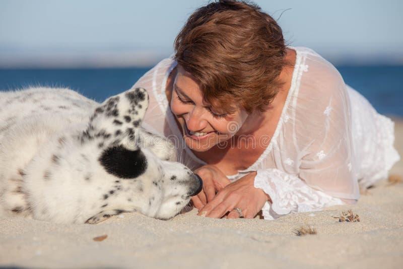 Houdende van hondeigenaar bij strand stock fotografie