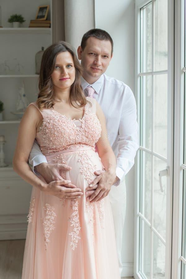 Houdende van man die zwangere vrouw omhelzen royalty-vrije stock fotografie