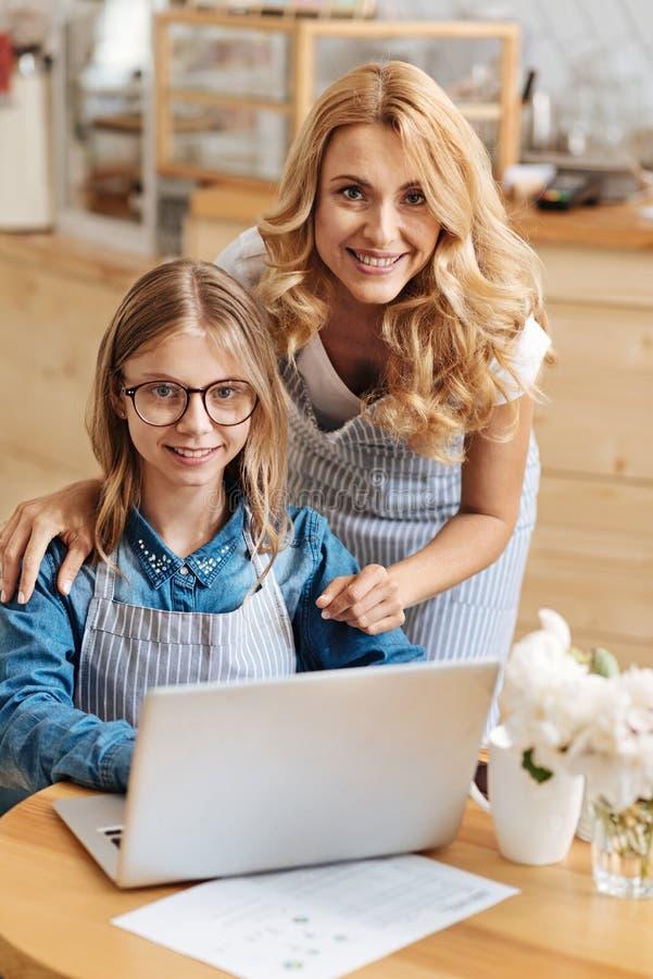 Houdende van moeder die haar dochter koesteren die aan laptop werken stock foto