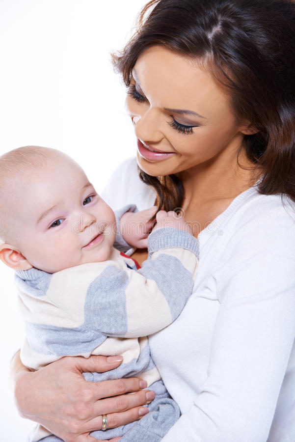 Houdende van moeder die haar gelukkige babyzoon wiegen stock foto