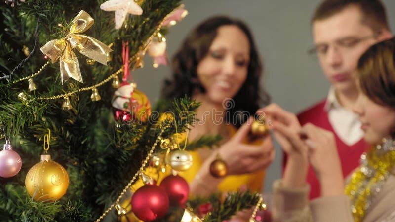 Houdende van ouders die hun dochter helpen om Kerstboom, magische ogenblikken te verfraaien royalty-vrije stock afbeelding