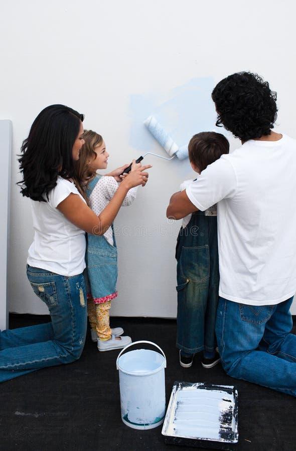 Houdende van ouders die hun kinderen helpen te schilderen stock foto