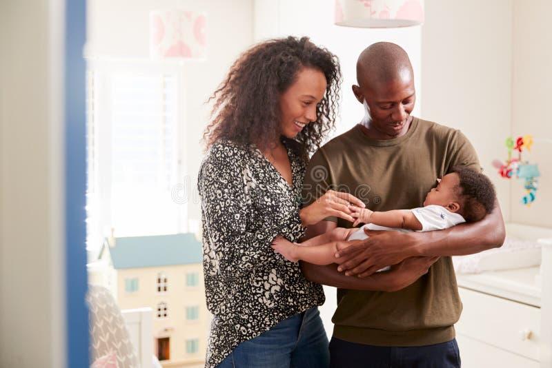 Houdende van Ouders die in Zoon van de Kinderdagverblijf de Knuffelende Baby zich thuis bevinden royalty-vrije stock afbeeldingen