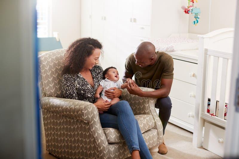 Houdende van Ouders die in Zoon van de Stoel de Knuffelende Baby in Kinderdagverblijf thuis zitten stock afbeeldingen