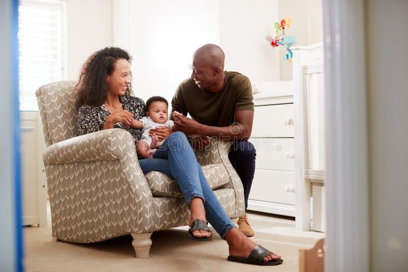 Houdende van Ouders die in Zoon van de Stoel de Knuffelende Baby in Kinderdagverblijf thuis zitten royalty-vrije stock foto