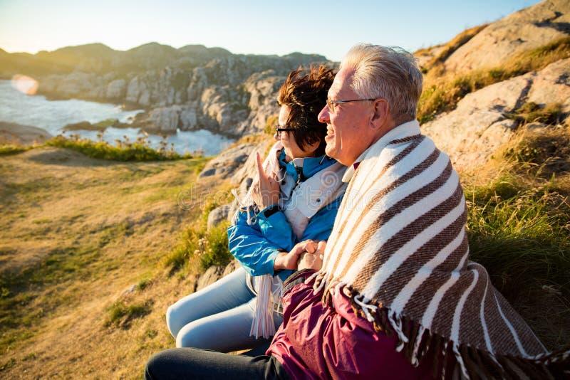 Houdende van rijpe paar wandeling, die op winderige bovenkant van rots zitten royalty-vrije stock foto's