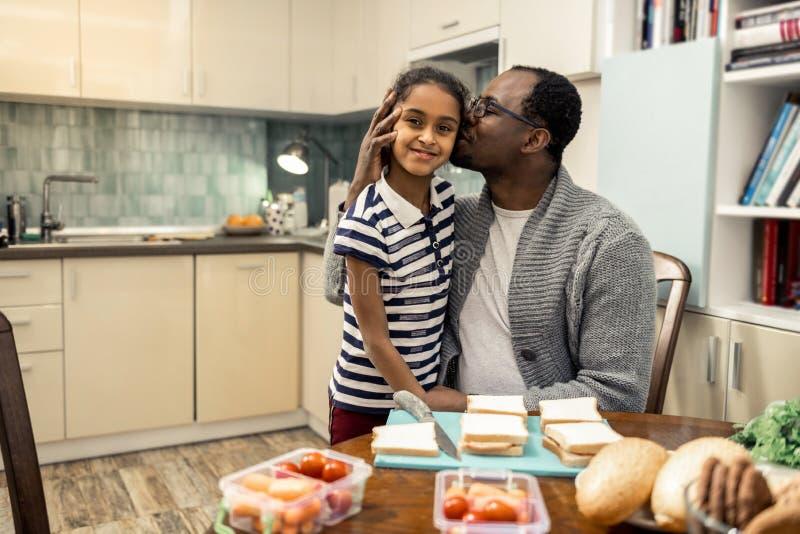 Houdende van vader die glazen dragen die zijn mooie jongere dochter kussen royalty-vrije stock foto