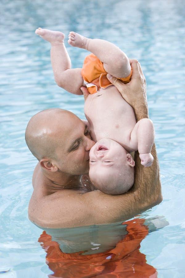 Houdende van vader en baby die pret in zwembad hebben stock foto