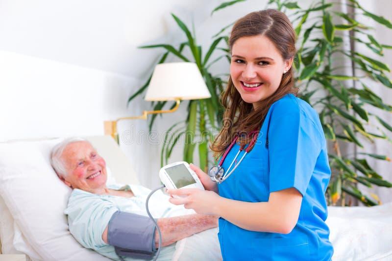 Houdende van verzorger die bloeddruk meten stock afbeelding