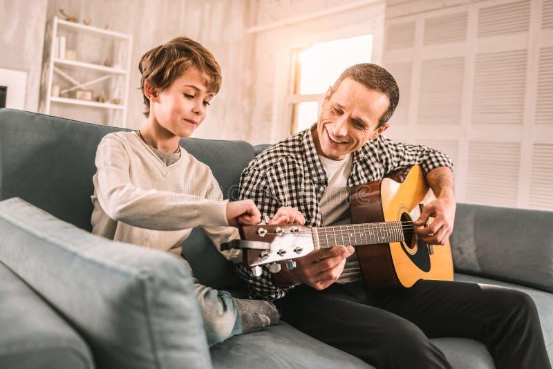 Houdende van zoon die om hulp van zijn papa op een muziekklasse vragen stock fotografie
