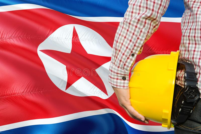 Houdt de het noorden Koreaanse Ingenieur gele veiligheidshelm met golvende de vlagachtergrond van Noord-Korea Bouw en de bouwconc royalty-vrije stock afbeelding