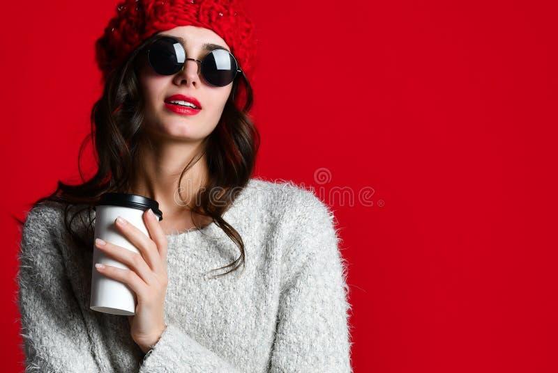 Houdt de manier gelukkige glimlachende vrouw koffiekop op rode muurachtergrond stock foto