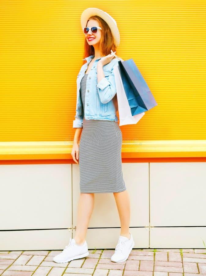 Houdt de manier glimlachende vrouw het winkelen zakken, strohoed op sinaasappel stock foto's