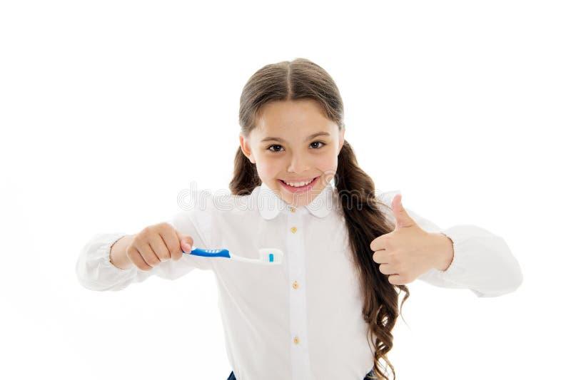 Houdt de meisjes briljante perfecte glimlach tandenborstel met daling van deeg witte achtergrond Het kind houdt tandenborstel en  stock afbeeldingen