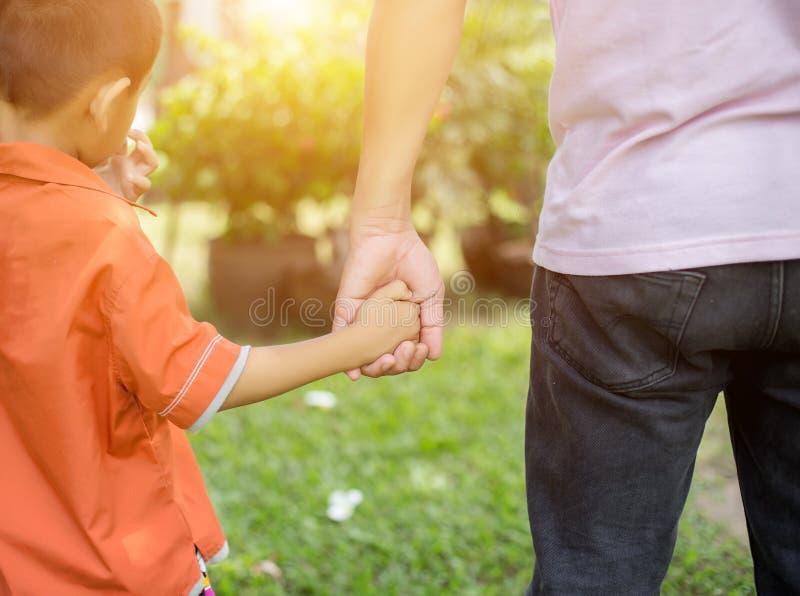 Houdt de ouder de hand van een klein kind royalty-vrije stock afbeeldingen