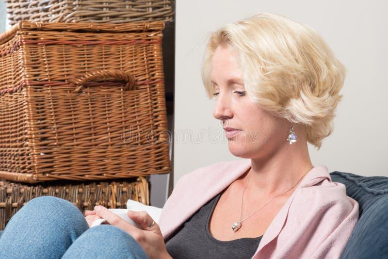 Houdt de terloops Geklede Blondevrouw thuis Mok terwijl het Denken royalty-vrije stock afbeeldingen