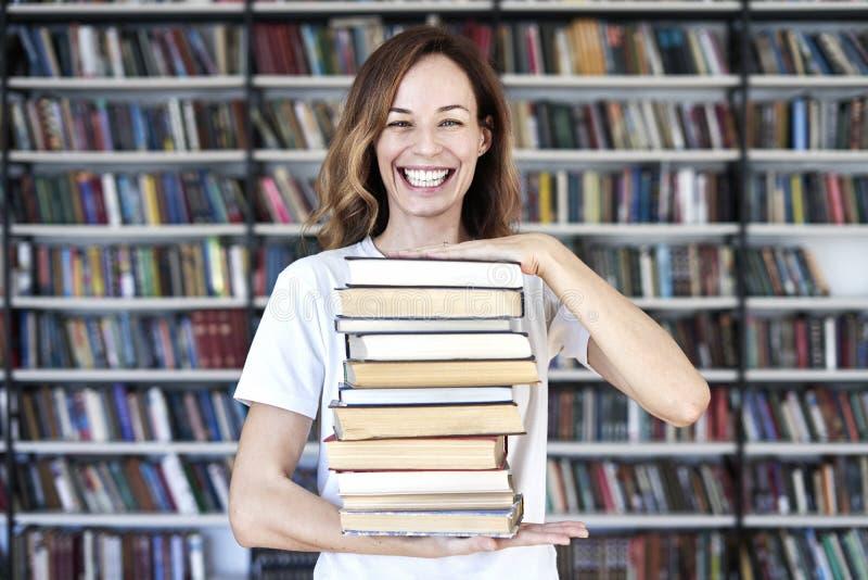 Houdt de vrouwen modelstudent bij bibliotheek bos van boeken, glimlachend aan camera boekenrekken bij de bibliotheek royalty-vrije stock afbeeldingen