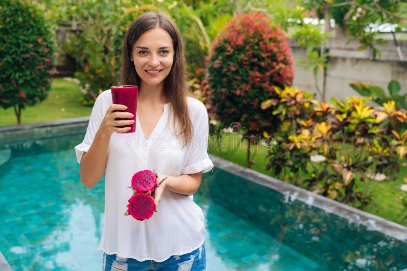 Houdt het portret vegetarische meisje in haar handenglas van smoothie en draakfruit royalty-vrije stock afbeelding