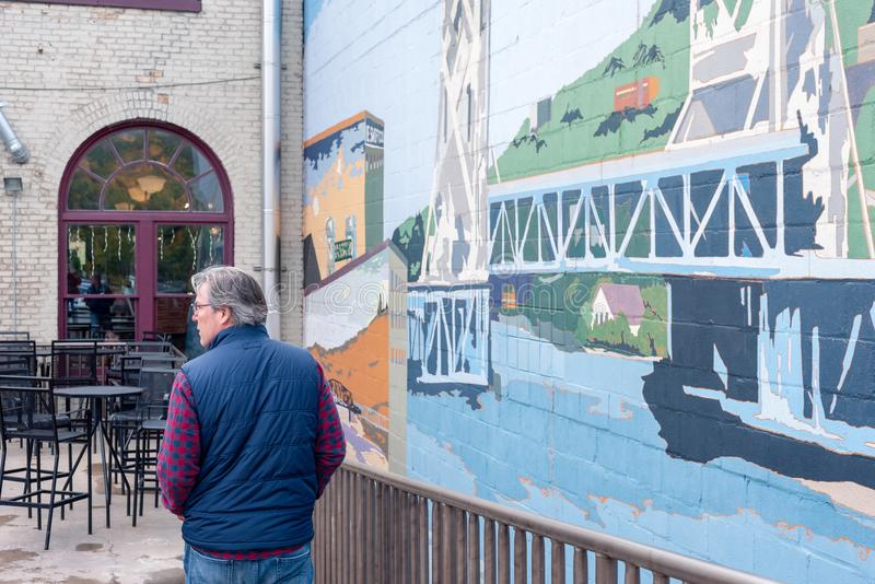 Houghton, MI/USA - 10-06-2018: Keweenaw Brewing Company, man walking by mural on outdoor patio. Houghton, MI/USA - 10-06-2018: Keweenaw Brewing Company, man in royalty free stock photo