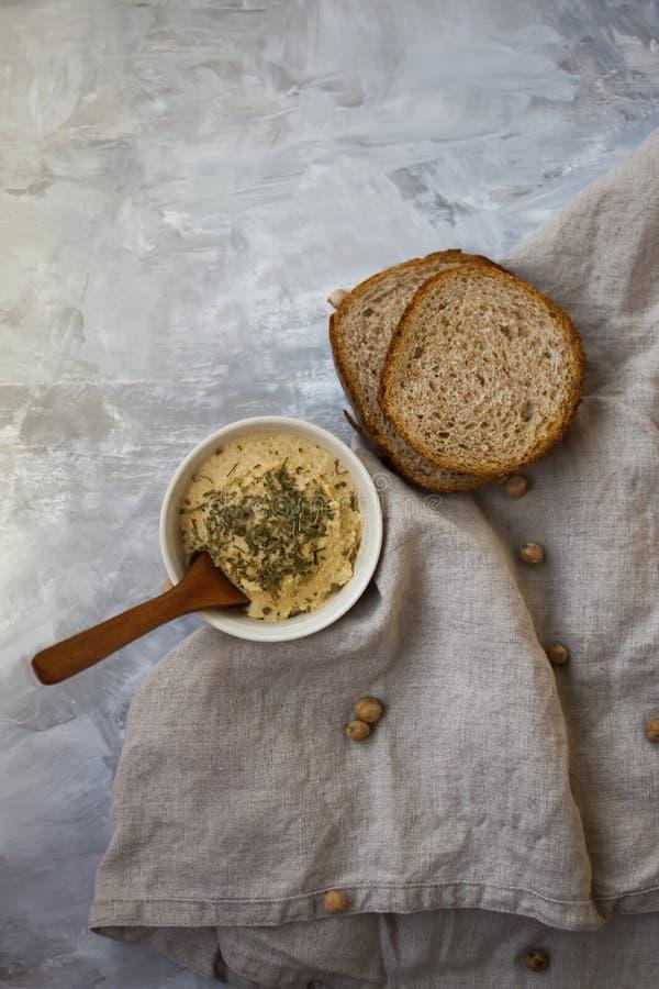 Houmous avec des herbes à côté de pain cuit au four frais images libres de droits