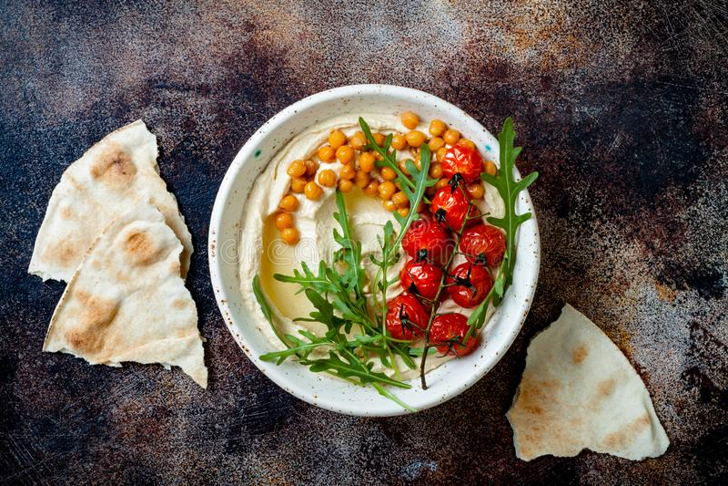 Houmous fait maison avec les tomates-cerises et les olives r?ties Cuisine arabe traditionnelle et authentique du Moyen-Orient images libres de droits
