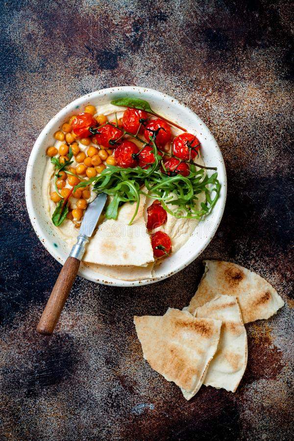 Houmous fait maison avec les tomates-cerises r?ties Cuisine arabe traditionnelle et authentique du Moyen-Orient photos stock