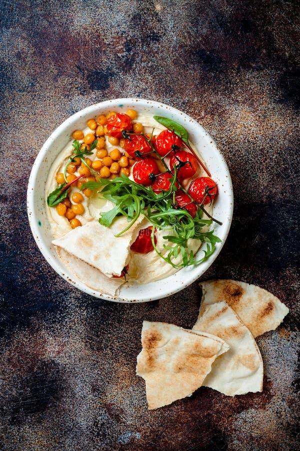 Houmous fait maison avec les tomates-cerises r?ties Cuisine arabe traditionnelle et authentique du Moyen-Orient image libre de droits