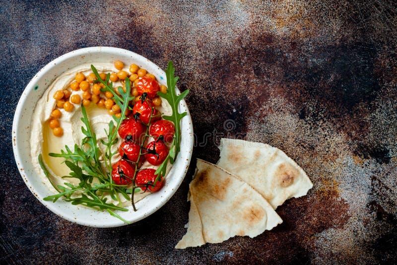Houmous fait maison avec les tomates-cerises r?ties Cuisine arabe traditionnelle et authentique du Moyen-Orient photographie stock libre de droits