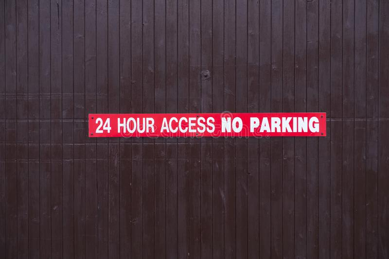 24 hour access no parking sign red and white on wooden access door. Uk vector illustration