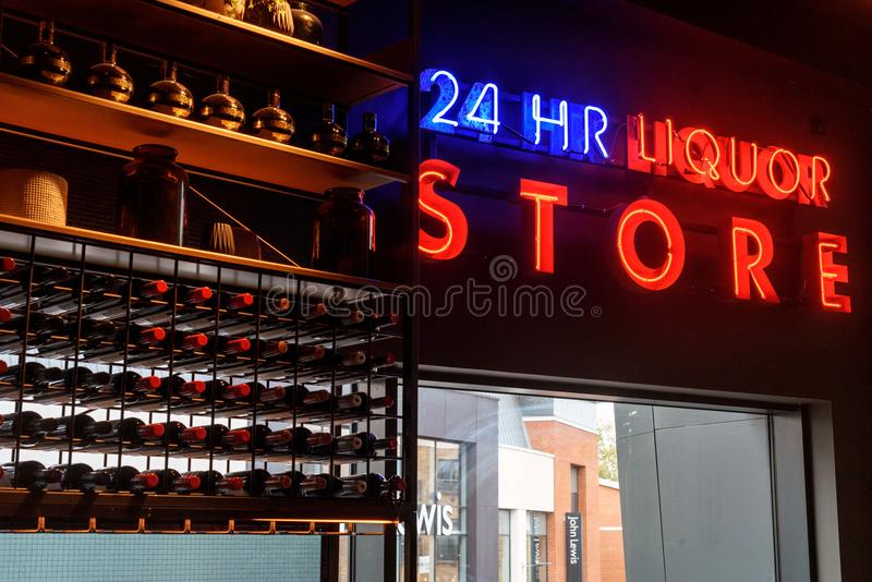 24 Hour Alcohol on Display at a Bar. Rows of bottles of alcohol on display at a bar with nobody with 24 hour liquor neon sign royalty free stock photography