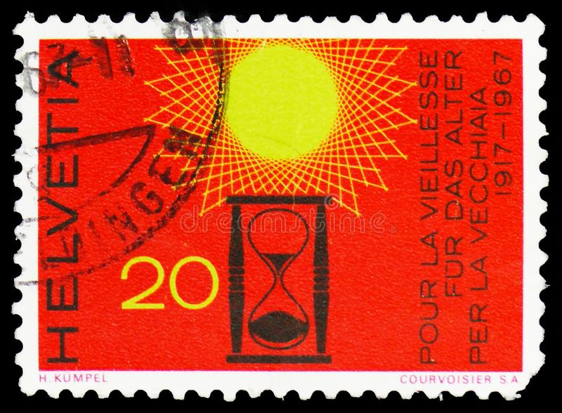 Hour glass under a stylised sun, Current Events serie, circa 1967. MOSCOW, RUSSIA - FEBRUARY 22, 2019: A stamp printed in Switzerland shows Hour glass under a royalty free stock images