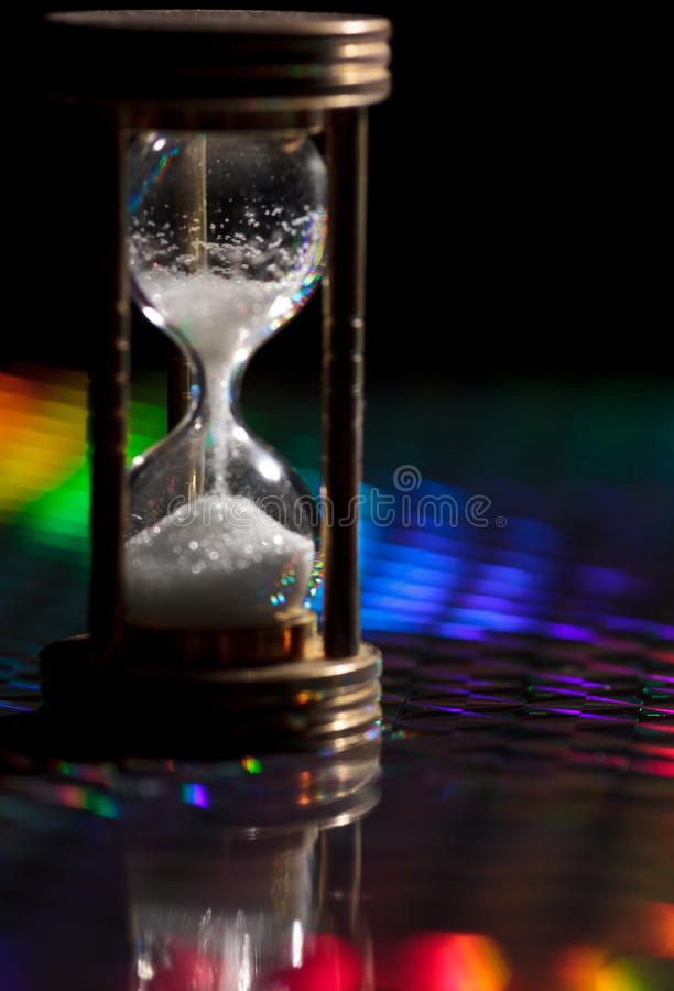 Hourglass. Wood and glass hourglass on colorful background stock photography