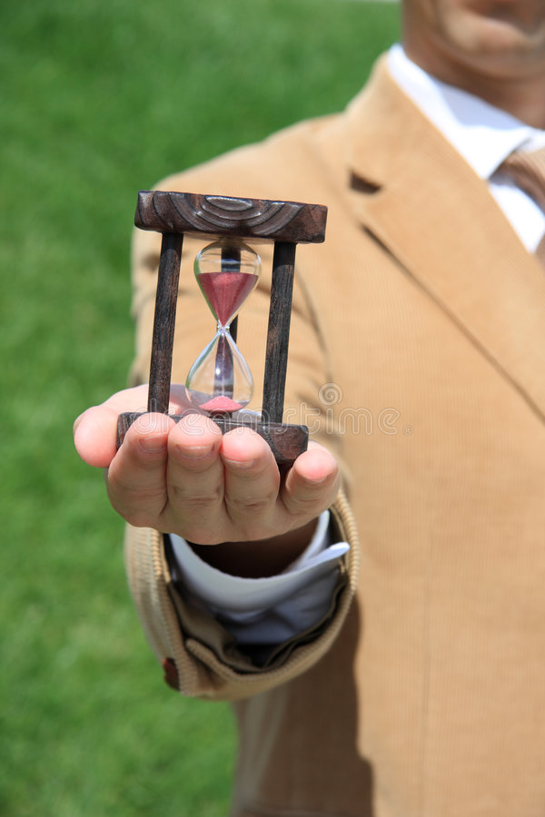 Hourglass. A business man holding a wooden hourglass on his hand royalty free stock photo