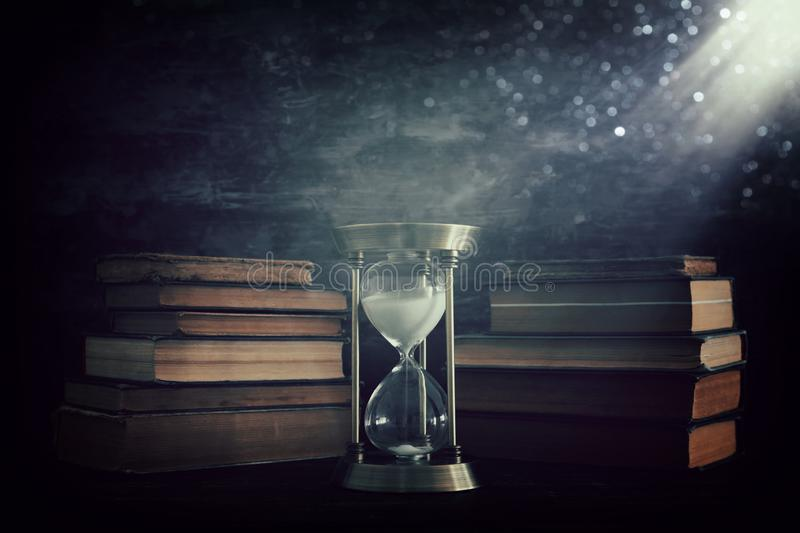 Hourglass as time passing concept and old books in front of black wall background. Conceptual photo on history, fantasy and vector illustration
