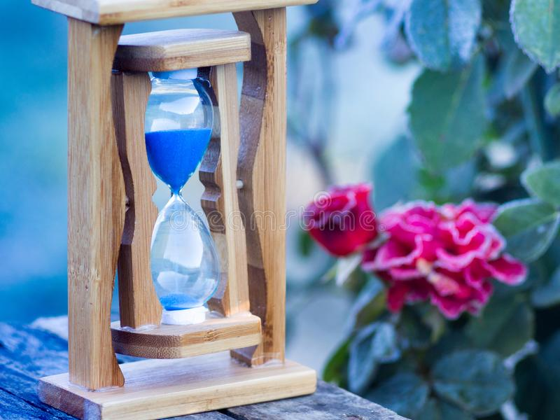 Hourglass on the background are covered with frost of rose flowers. Fluctuation of time_. Hourglass on the background are covered with frost of rose flowers stock images