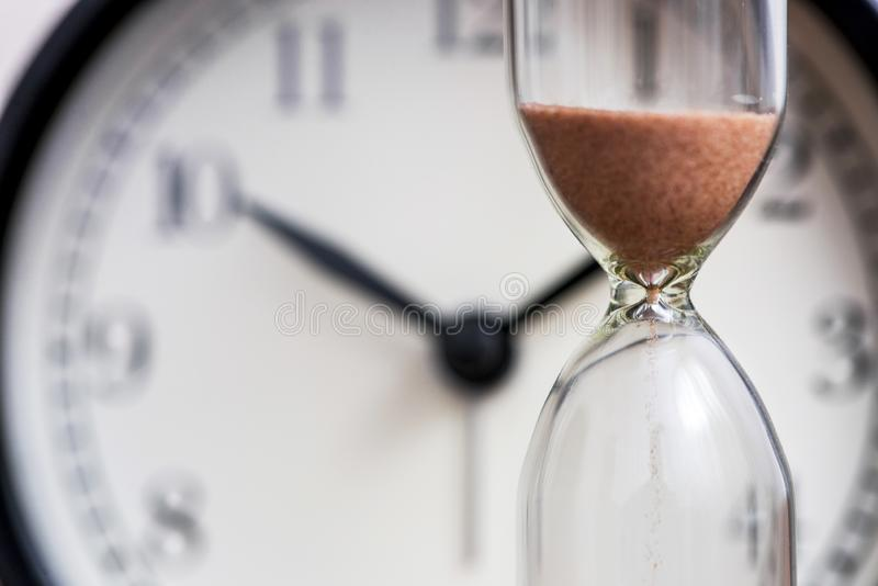 Hourglass on the background of office watch as time passing concept for business deadline, urgency and running out of time. Sand stock image
