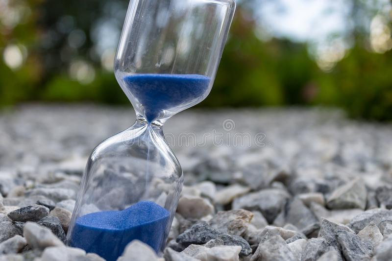 Hourglass with beautiful blue sand lie on small stones royalty free stock image