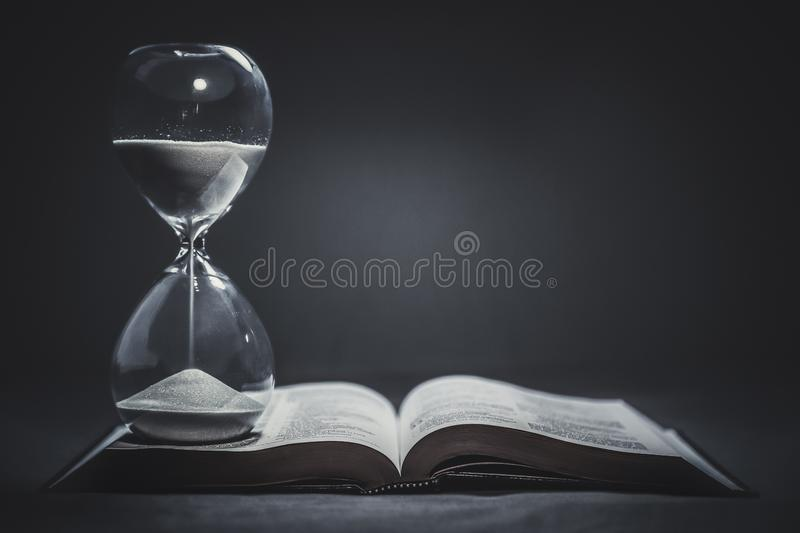 Hourglass on a Bible stock photography