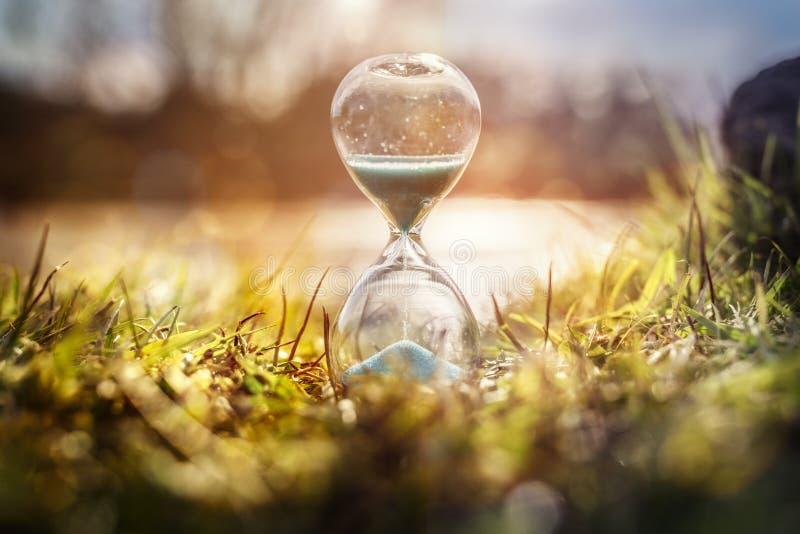 Hourglass bij zonsondergang concept voor tijdverdrijving stock foto